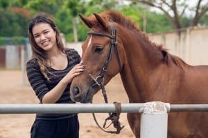 young woman with her horse during equine therapy