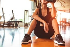 young woman taking a drink of water as she pairs exercise and addiction recovery
