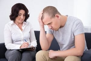 young man and female therapist participating in PTSD therapy in a PTSD treatment program